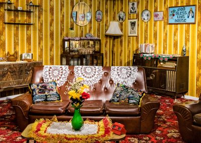 Vibrantly Coloured Front Room With Yellow Wallpaper, Red Patterned Carpet And Lace Anti-macassars On The Sofa.